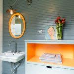 bathroom color trends wall mounted sink round mirror hanging lamp orange shelf white tile grey backsplash contemporary design