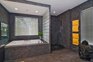 bathroom with bathtub, shower without door, dark mosaic tiles on flooring, wall, metal shower fixture