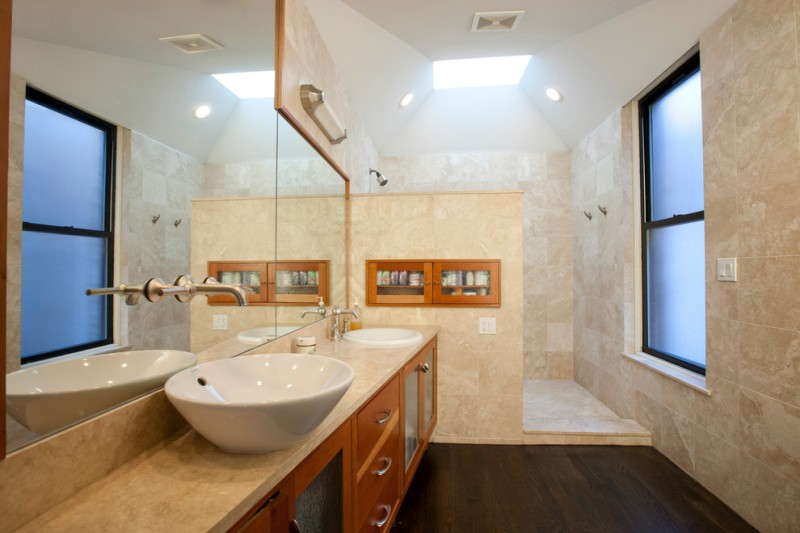 bathroom with walk in shower with cream tiles one the wall, built in cabinet on the wall, white sink, white bowl sink, wooden cabinet under the sink