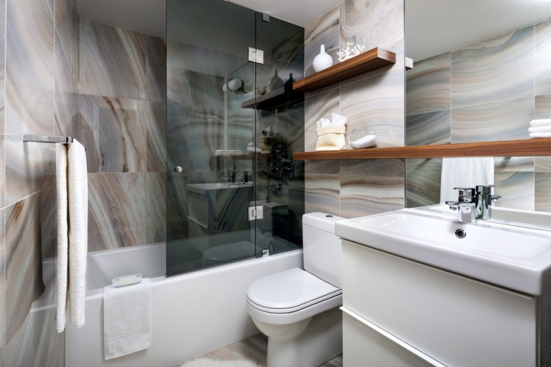 bathroom with white whitetub also for shower with grey finish glass partition, porcelain tile flooring and wall, wooden shelves, white sink, toilet, and cabinet