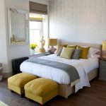 Beach Themed Bedroom Design With Textured And Silver Wallpaper Grey And Mustard Yellow Bed Accessories A Couple Of Yellow Ottoman Chairs Dark Hardwood Floors Grey Bedside Tables Silver Framed Mirror
