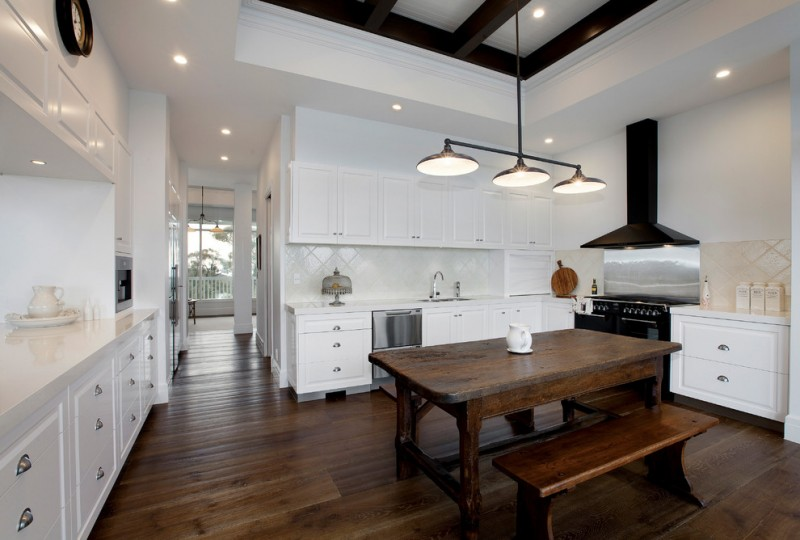 bench style kitchen tables hardwood floor wooden table chandelier ceiling lamps wall cabinets drawers stove faucet sink clock farmhouse style