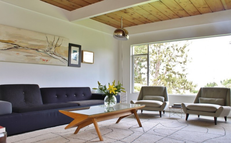 black soffa mid century coffee table wall artwork cream rug gray chairs hanging lamp white wall wooden deck ceiling