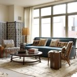 Blue Sofa Accents Chairs Cream Rug Round Coffee Table Wooden Room Divider Cream Curtains Wall Table Lamps
