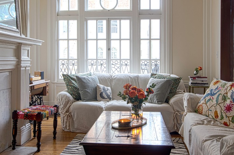 boho chic furniture sofas pillows wooden table flowers small table books window living room