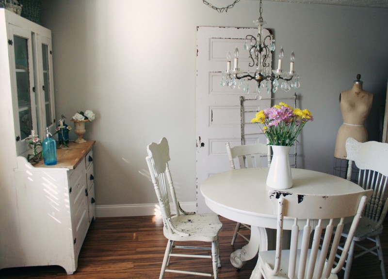boho chic furniture tall back chairs wood floor cabinet drawers round top table flowers chandelier dining room