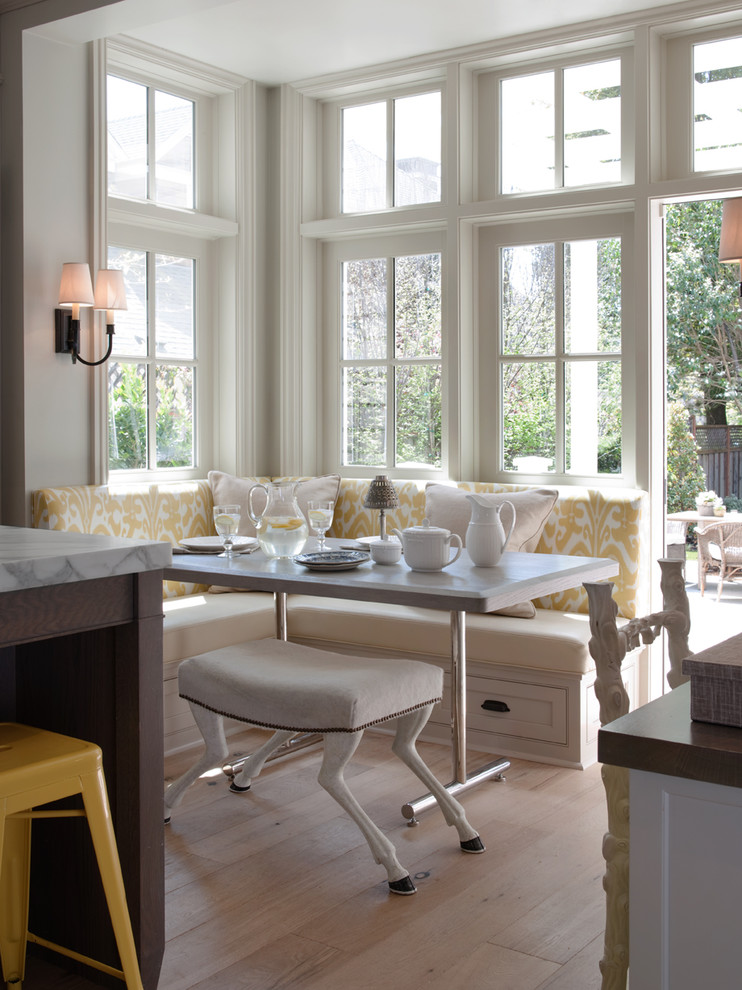 breakfast nook benches shaggy ottoman wall lamps marble countertop cabinets stool dining table hardwood floors white walls traditional design