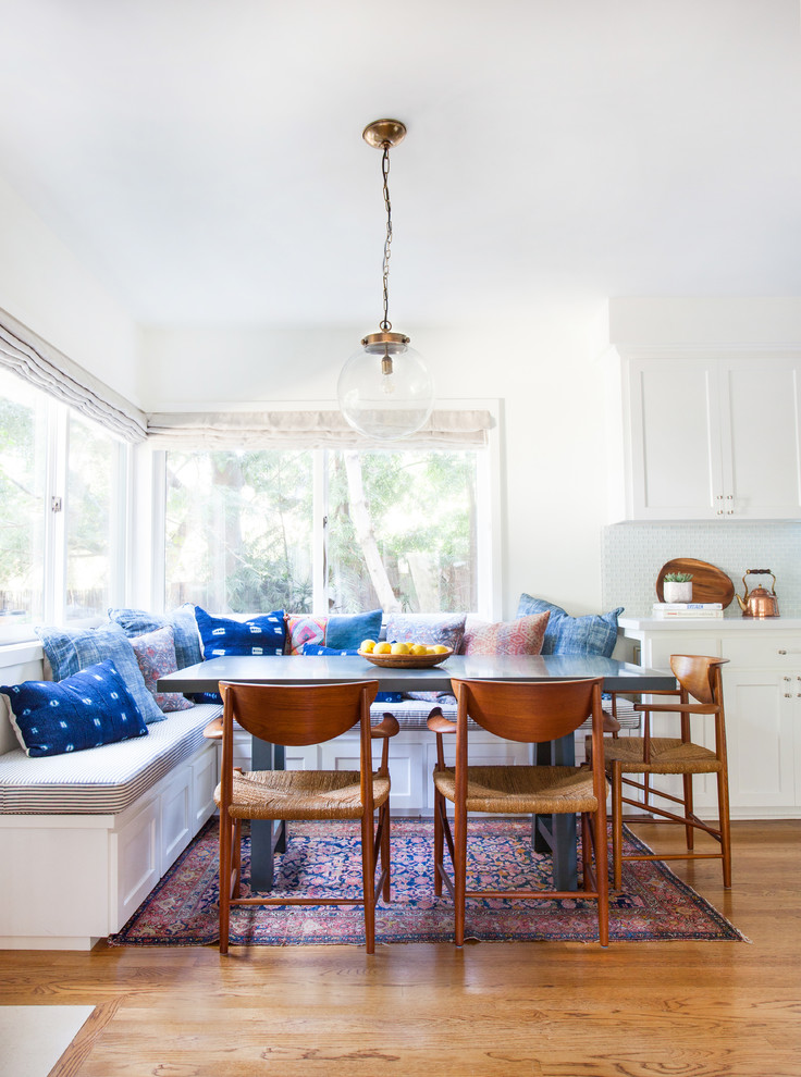 breakfast nook benches shaker cabinets dining table low back chairs modern pendant carpet throw pillows medium tone hardwood floors eclectic design