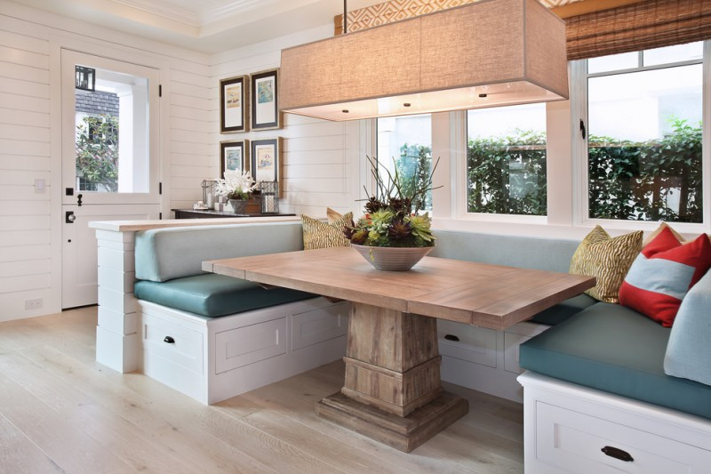 breakfast nook benches subway tiles built in drawers cabinet wood table chandelier throw pillows blinds hardwood floors traditional design