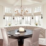 Breakfast Nook Benches Tall Back Chairs Chandelier Wall Lamps Wood Table Flower Vases Centerpiece Hardwood Floors Traditional Design