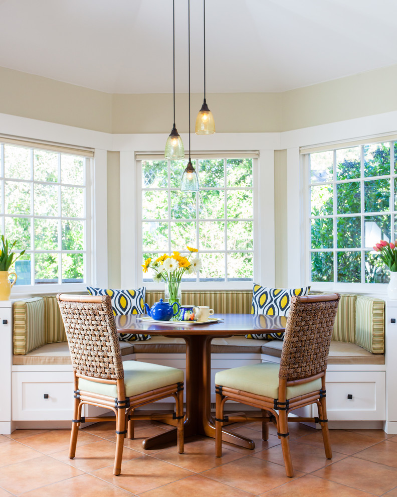 breakfast nook benches tall back chairs wood table throw pillows modern pendants terra cotta floors flower centerpiece traditional design