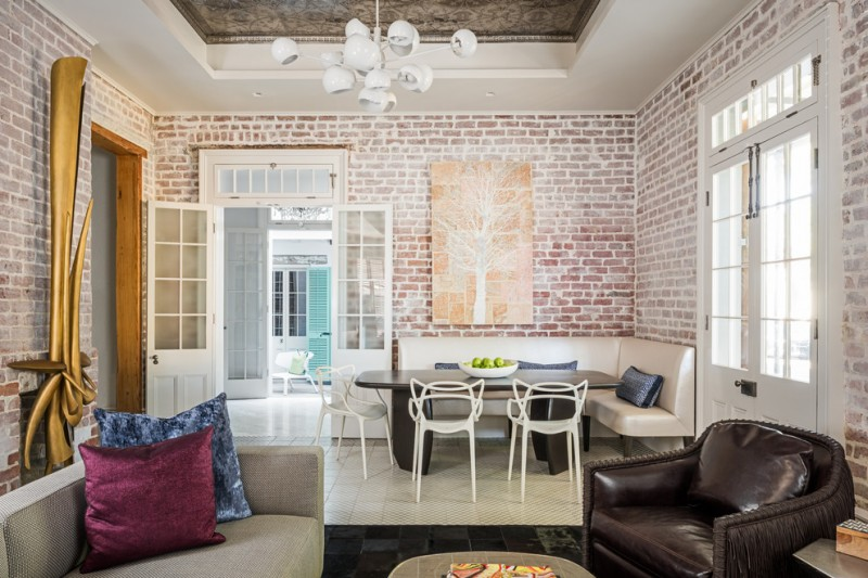 breakfast nook white chair dark brown table black white tiles pillow throws brick wall letter couch sofa wall art