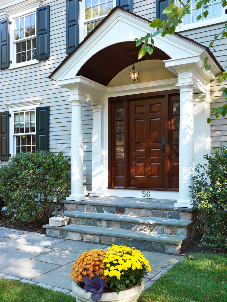 brown wooden colonial front door with beautiful portico with stones, vertical glass window