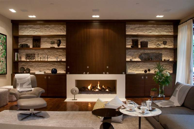 built in cabinet flat panel shelves fireplace stone backwall contemporary chair gray sofa rounded table wooden floor