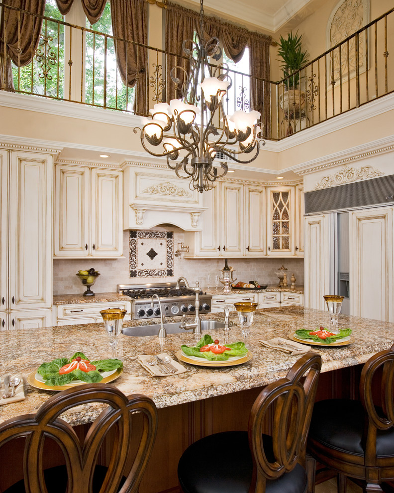 calypso home furniture chandelier granite countertop dining table tall back chairs ornate white cabinets undermount sink subway tile backsplash appliances traditional design