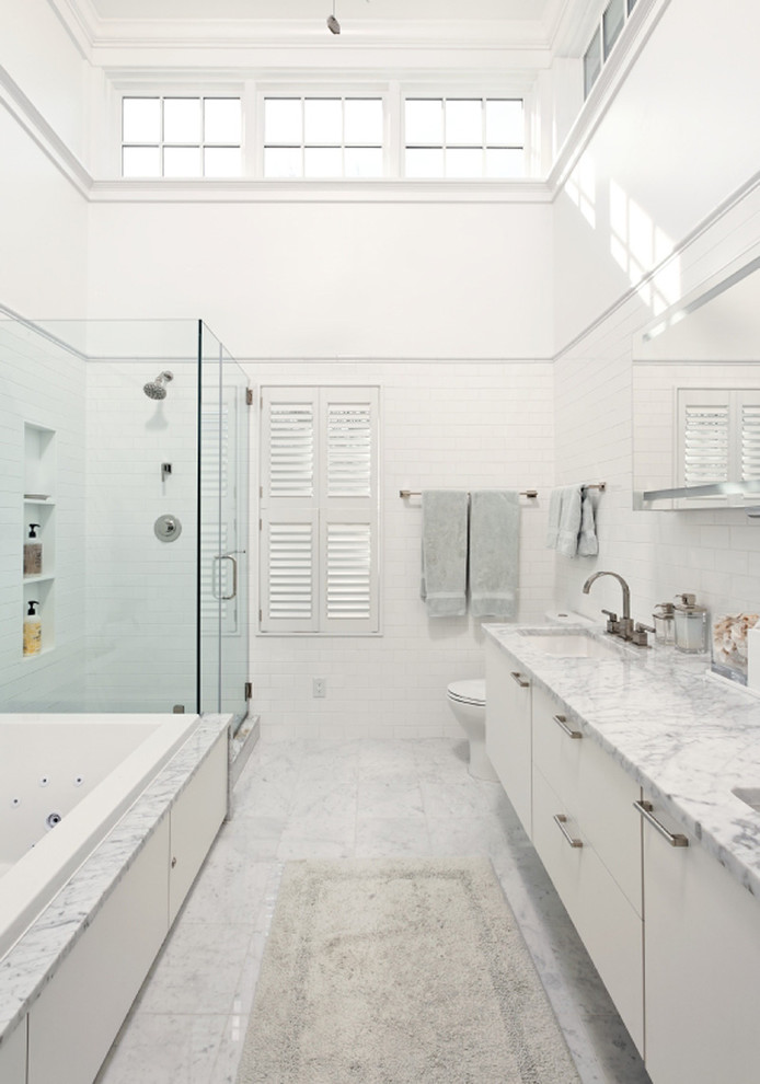 carrera marble bathrooms subway tiles drop in tub undermount cabinets countertops two piece toilet glass door alcove shower white walls sink contemporary design