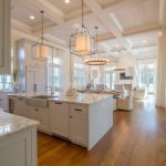 Clean White Kitchen Island With White Marble Top Farmhouse Sink And Stylish Cabinets
