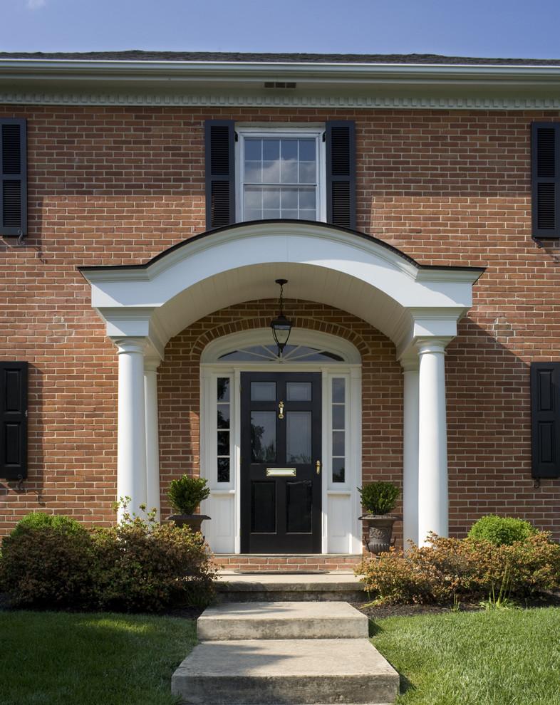 colonial front doors with storm door in front of it