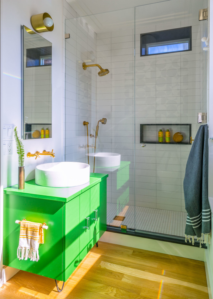 contemporary bathroom idea green vanity with white sink and gold toned faucet gold toned vanity lamp medium toned wood floors shower glass panel white ceramic shower walls white ceramic tiles floors