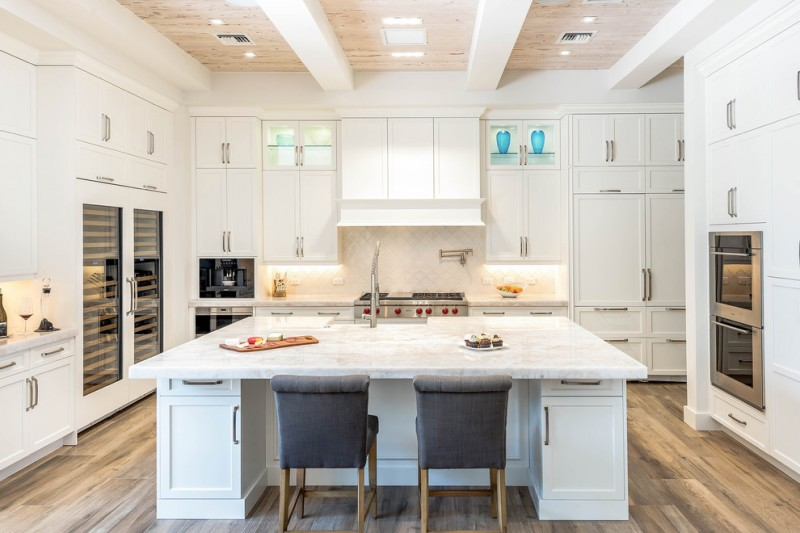 contemporary kitchen design in dominant white white kitchen island with cabinets addition a couple of grey chairs with wood foot wood floors without finishing