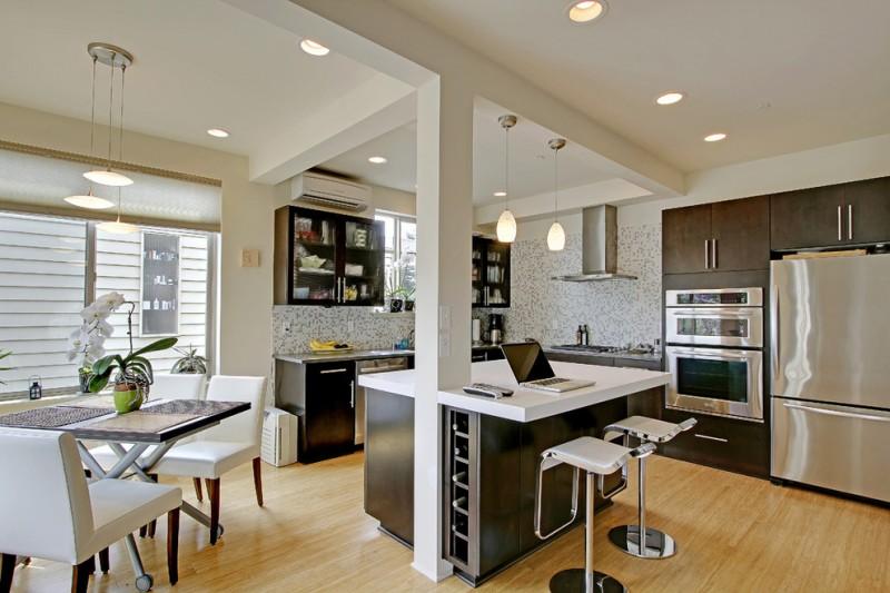 contemporary kitchen island in monochromatic side wine shelves modern bar stools medium toned wood floors