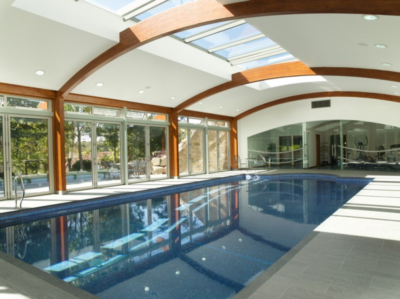 curved pool enclosure with beams white tiles flooring system glass windows