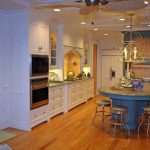 custom made kitchen islands marble countertop stools white cabinets yellow backsplash paneled appliances built in refrigerator hook ceiling lights fan hardwood floors tropical style