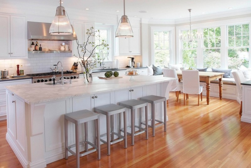 custom made kitchen islands marble countertops wooden table tall back chairs bar stools subway tiles white backsplash single hole sink recessed panel cabinets traditional design