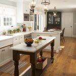 Custom Made Kitchen Islands Shaker Cabinets Farmhouse Sink Standing Bookshelves Stainless Steel Appliances Ceramic Backsplash Hardwood Floors Modern Pendants Traditional Design