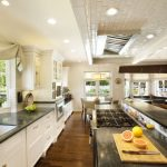 custom made kitchen islands undermount sink soapstone countertops recessed panel cabinets round dining table low back chairs subway tile backsplash ceiling lights hardwood floors beach style