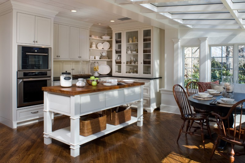 custom made kitchen islands wood countertop glass front cabinets stainless steel appliances round dining table tall back chairs ceiling lights hardwood floors traditional design