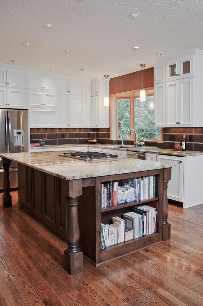 dark toned wood kitchen island with marble top and side book shelves glossy wood floors stainless steel appliances L shaped kitchen with white upper and lower cabinets black ceramic tiles backsplash