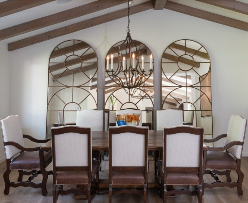 decorative mirrors for dining room candle holder chandelier narrow table tall back armchairs hardwood floors white walls mediterranean design