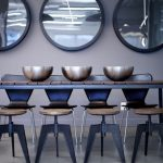 decorative mirrors for dining room wood tabletop tall back chairs circular bowls classic pendants beige walls concrete floor modern design