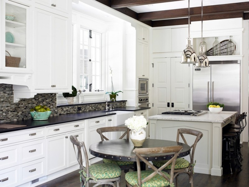 farm style kitchen table dark hardwood floor round top table old looking chairs backsplash wall cabinets window pendant lights flowers drawers dark countertop transitional room