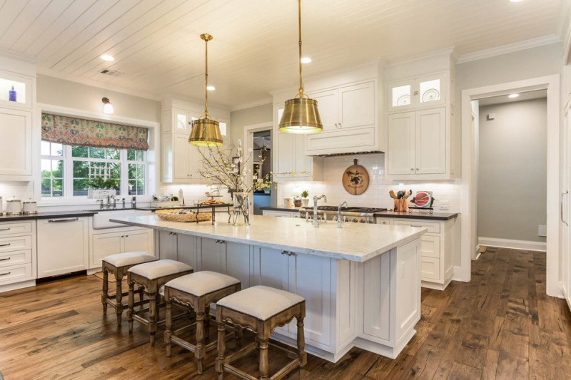 farmhouse kitchen with white kitchen island completed with storage and chairs L shaped black countertop white cabinets white ceramic backsplash country style window curtains wood floors without fi