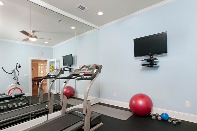 floor to ceiling mirror dumbbells baseboards ceiling light wall tv treadmill gym ball traditional home gym