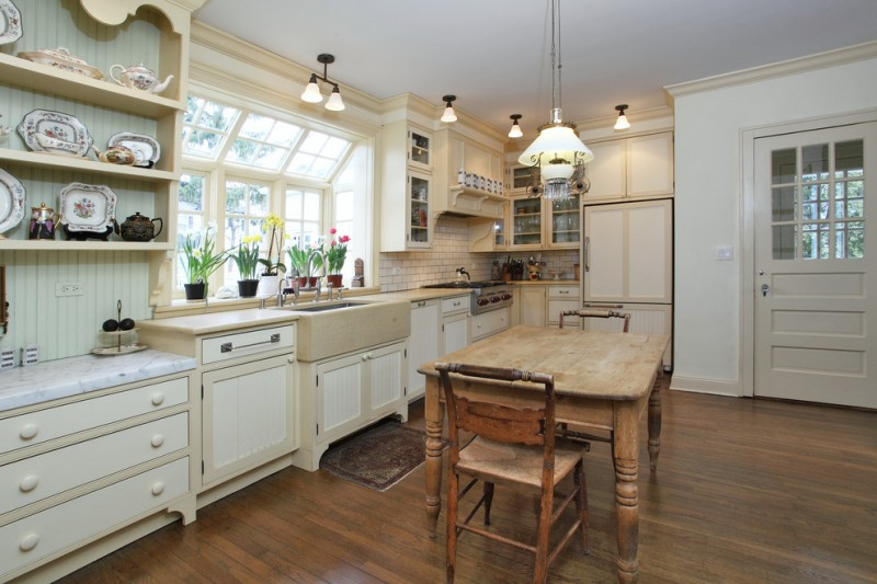 garden windows for kitchen subway tiles hanging shelves raised panel cabinets wood table dining chairs single hole sink ceiling lights white pendants hardwood floors traditional design