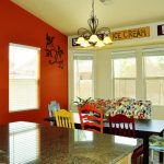 good colors for kitchens granite countertops raised panel cabinet chandelier narrow wood table bench colorful chairs throw pillows red walls decorative mirror eclectic design