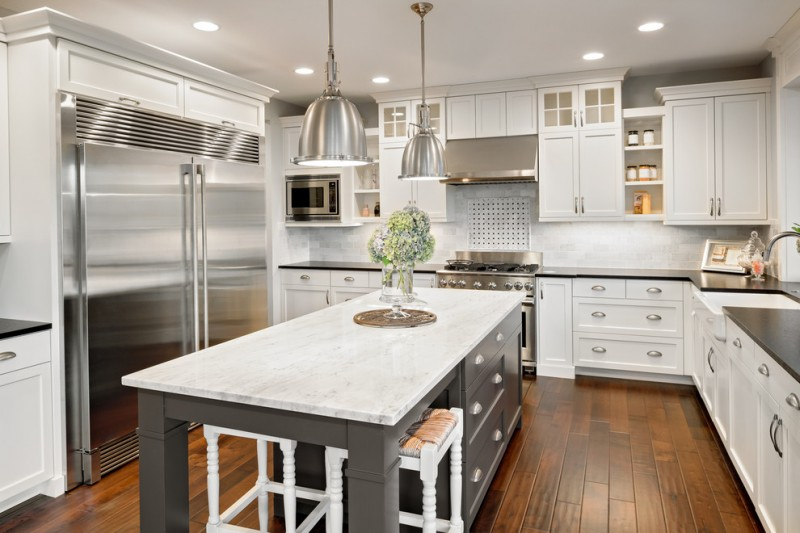 grey kitchen island with storage and white marble top L shaped kitchen with silver toned countertop white cabinets white backsplash stainless steel appliances dark hardwood floors
