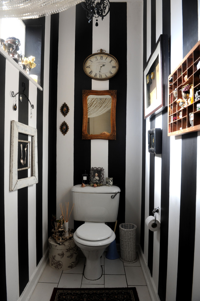 guest bathroom idea in monochromatic vertical stripes theme two piece toilet in white some framed wall arts white ceramic tiles floors