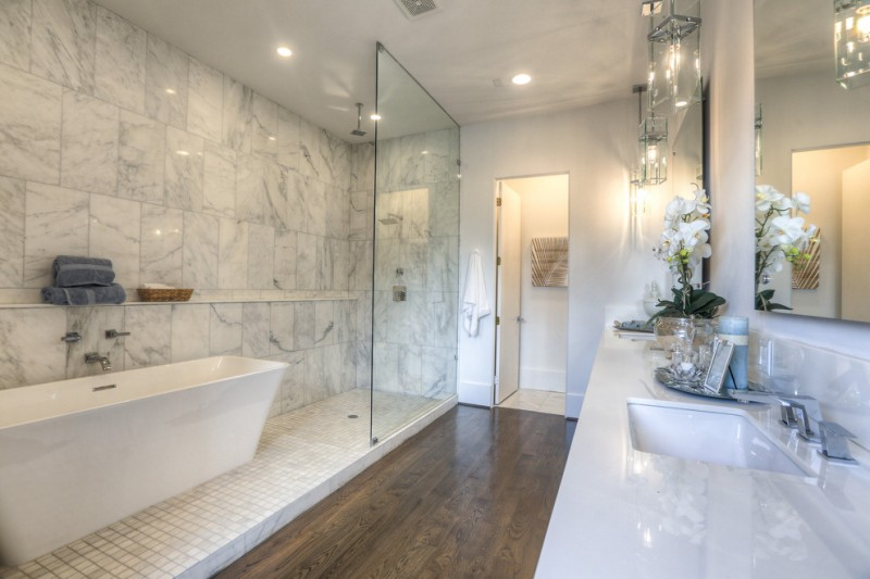 jacuzzi tub shower combo towels faucets cool lamps hardwood floor ceiling lights flowers transitional bathroom