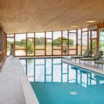 Large And Modern Pool With Huge Wood Enclosure Clean White Concrete Floors Glass Windows With Irregular Shaped Glass Panels