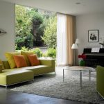 Light Green Yellow Couch With Colorful Pillows White Area Rug Music Corner White Orange Window Curtains White Painted Walls Concrete Floors
