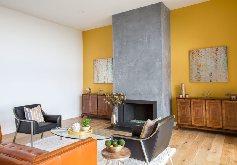 light yellow walls accented by original concrete mantel two abstract hand paintings old wood console tables black leather armchairs brown leather couch white area rug wood floors without f
