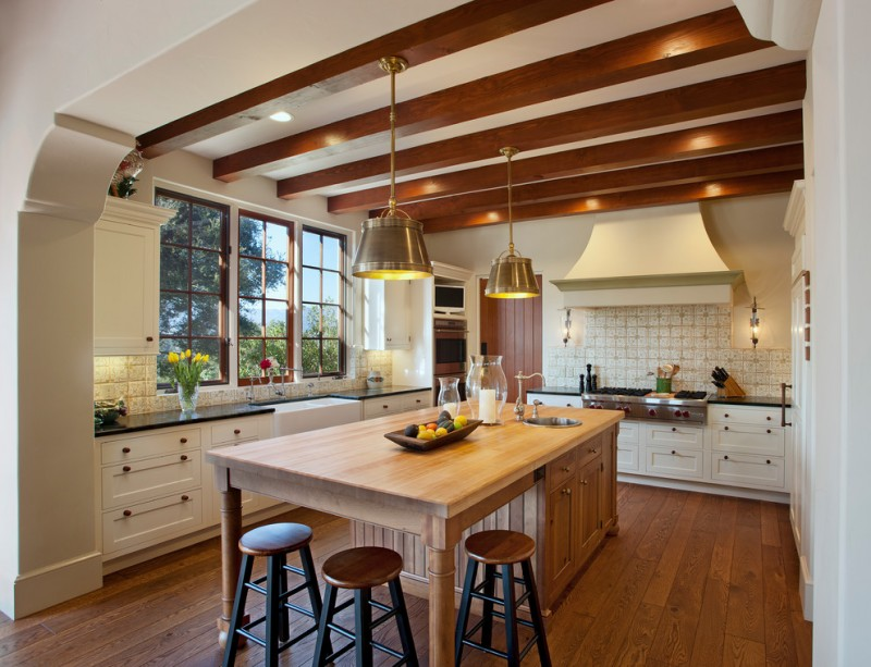 mediterranean style kitchen unfinished and craftman kitchen island equipped with cabinets and undermount sink L shaped & black countertop white cabinets white tiles backsplash with pattern