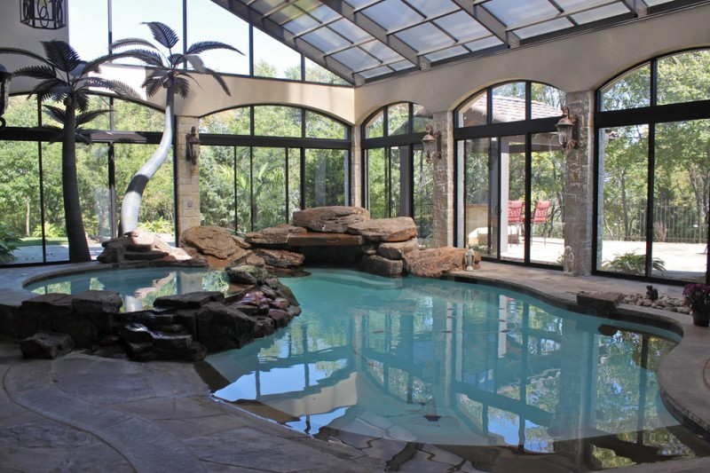 mediterranean style pool with glass sliding roof and walls natural stones flooring idea artificial tropical trees