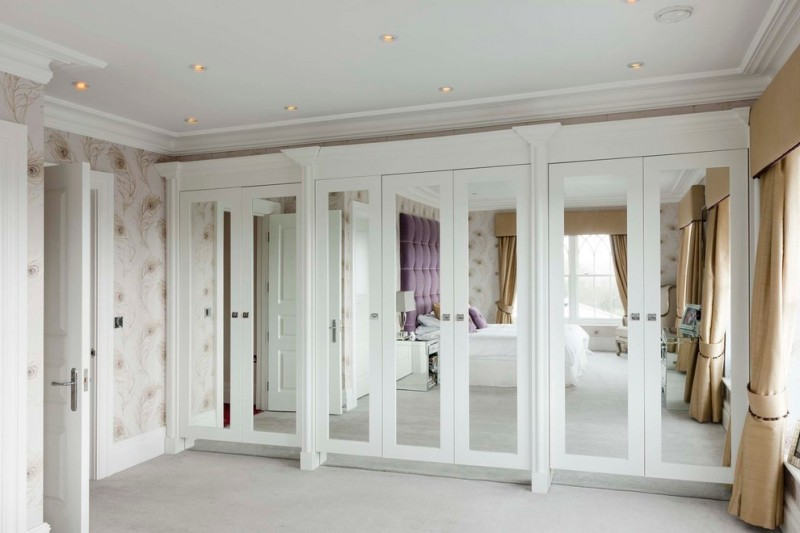 mirrored French closet doors white paint multicolored wall beige rug brown curtain table lamp glass surface cabinet