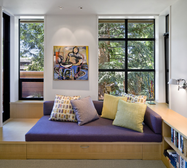modern family room with wood bench integrated with book shelves purple bench comforter purple & yellow decorative pillows light grey walls