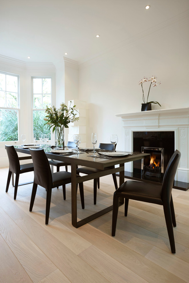 modern formal dining room set light coloured floor simple table dark chairs modern fireplace windows flowers ceiling lights